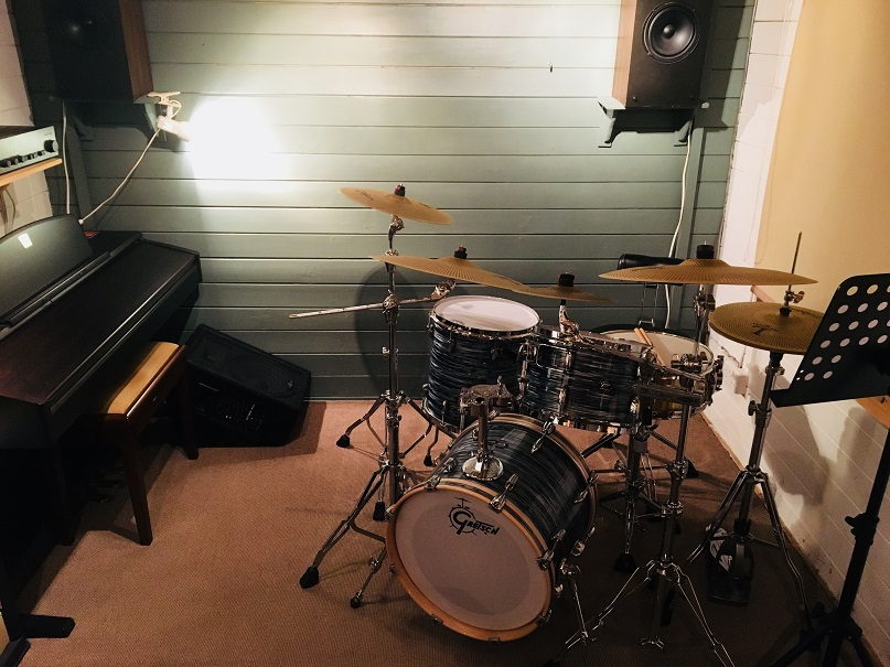 A studio, with a piano against the left wall and a drum kit to the right.